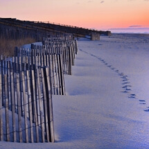 image of footprints and fence at the beach